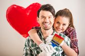 picture of mischief  - Portrait of young happy couple painted a heart on the wall while doing repair at home and looking at the camera - JPG