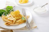 Pancakes With Honey And Sour Cream On A Plate