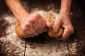 Baker Hands With Fresh Bread On Table