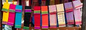 picture of dupatta  - Various colorful fabrics and shawls at a market stall - JPG