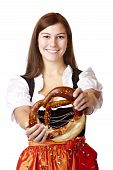 Portrait of young woman with Bavarian Dirndl dress holds Oktoberfest Pretzel.