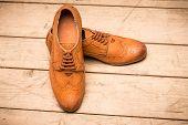 foto of ginger man  - Elegant Men Brown Shoes on wooden background - JPG