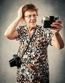 Granny photographer make selfie. Old woman with camera. Senior studio shot
