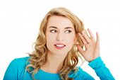 Woman listening gossip with her hand next to her ear