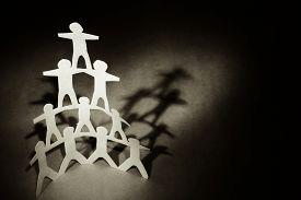 picture of human pyramid  - Human team pyramid on dark background - JPG