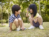 stock photo of playmates  - little asian girl looking at little asian boy through a magnifier outdoors in a park - JPG