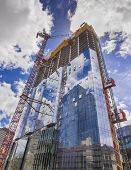 image of construction crane  - Construction site of new glass skyscraper with cranes on sky background - JPG