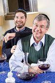 Senior Jewish Man, Adult Son Celebrating Hanukkah