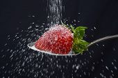 stock photo of sprinkling  - sugar rain sprinkle over delicious strawberry on spoon spilling out everywhere isolated on black background in natural sweet healthy nutrition concept