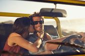 stock photo of driving  - Loving young couple on road trip. Woman kissing her boyfriend