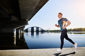 picture of leggins  - Young handsome man running along the embankment near the river under the bridge - JPG