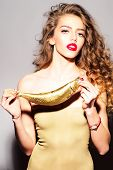 pic of fish skin  - Pretty young woman with curly hair in beige skin dress holding golden fish looking forward standing on grey background vertical picture - JPG
