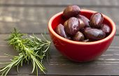 image of kalamata olives  - A bowl of olive on a wooden board with rosemary