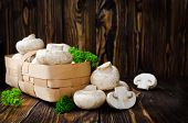 pic of champignons  - Champignons with parsley in a basket on a wooden table - JPG