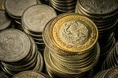 foto of golden coin  - A golden coin with an eagle over stacks of silver coins business wealth and success concept - JPG