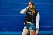 picture of rap-girl  - Happy young girl listening music  in headphones over blue wall background - JPG