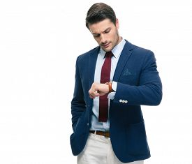 foto of retarded  - Confident businessman looking on his wrist watch isolated on a white background - JPG