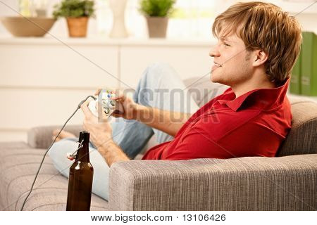 poster of Young man sitting on sofa playing computer game, smiling,?