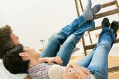 Couple lying relaxing with feet up on ladder, looking at painted walls at flat renovation.