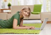 Happy blond woman lying on floor in living room browsing internet with laptop computer.