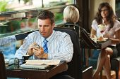 Businessman sitting at table in cafe using mobile phone. Young women having sweets in the background
