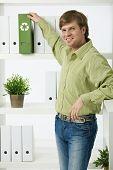 Homem jovem ambientalista no escritório retirando a pasta verde,