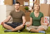 Young couple doing yoga meditation in new house after moving, sitting in middle of boxes.