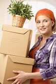 Smiling woman carrying boxes and plant at moving house.?