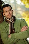Outdoors portrait of happy young man standing in autumn park at tree.?