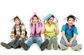 Educational theme: group of teenagers sitting together and holding books on their heads.