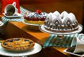 Still Life Of Gourmet Chocolate Cake, Fruit Tart, Blackberry Pie, And Coffee