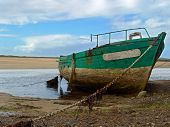 A Wreckage Of Boat Made Of Wood To Low Tide