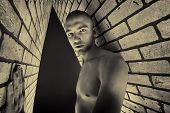 pic of skinhead  - Portrait of a handsome muscular man posing over black background and brick wall - JPG
