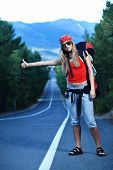 image of young adult  - Pretty young woman tourist hitchhiking along a road - JPG
