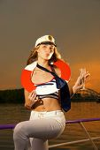 Attractive girl on a yacht with a life buoy on her neck