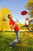Funny couple with umbrellas on autumn background