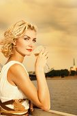 stock photo of merlin  - Beautiful blond girl drinks champagne near the river at sunset time - JPG