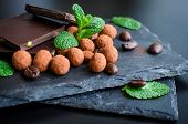 Heap Of Dark Chocolate Bars And Coffee Beans Candy Covered With Chocolate With Green Mint Leaves On  poster