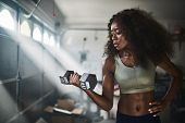 fit african american woman working out by lifting weights in home gym poster