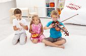 Kids trying to play on different musical instruments sitting on the floor
