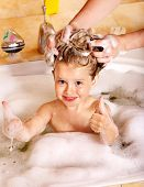 Child washing hair in bubble bath.