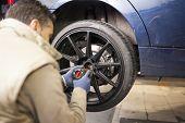 Mechanic Assembling Car Wheel In Mechanic Workshop poster