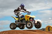 stock photo of dirt-bike  - Quad bike racing Airborne over a jump - JPG