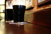 stock photo of guinness  - Two glasses of famous black Irish stout in Irish pub on wooden bar