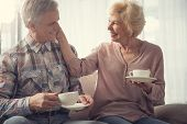 Smiling Senior Couple Relaxing With Cups In Arms And Staring At One Another With Amour. Female Perso poster