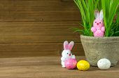 Pink And White Fuzzy Easter Bunnies With Candy Eggs And Grass In Flower Pot On Wood poster