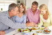 stock photo of portrait middle-aged man  - Mid age couples enjoying meal at home - JPG