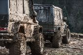 Suv Covered With Mud Stands Behind Another One. Dirty Offroad Cars On Dark Forest Background. Crosso poster