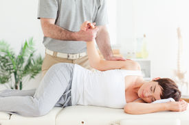 picture of chiropractor  - A chiropractor stretches a female customer - JPG