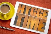 hygge time  word abstract in vintage letterpress wood type on a digital tablet with coffee, Danish l poster